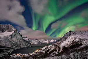 Aurora Borealis or northern lights over winter landscape