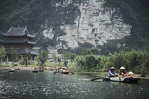 vietnamese kooplui in bootjes met op achtergrond tempel van