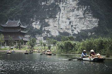 Marchands vietnamiens dans des bateaux avec un temple en arrière-plan sur
