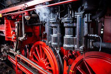 Stomende rijdende onderdelen en details van historische locomotief met rode spaak wielen van