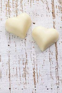 Twee witte chocolade harten op houten ondergrond