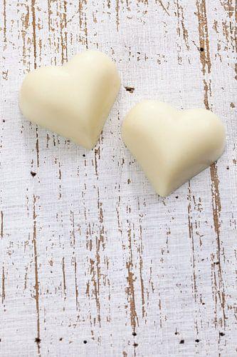 Twee witte chocolade harten op houten ondergrond van Beeldig Beeld