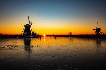 Kinderdijk in winter met schaatsers en zonsopkomst van Gert Hilbink