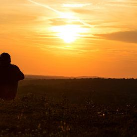 Ein Paar sitzt auf der Wiese und schaut in den Sonnenuntergang von Frank Herrmann