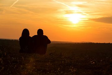 Een stel zit in de weide en kijkt in de zonsondergang... van Frank Herrmann