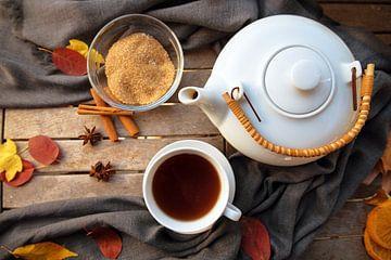 theekopje en een witte theepot op een houten tafel met specerijen en wat herfstbladeren, hoog hoekbe van Maren Winter
