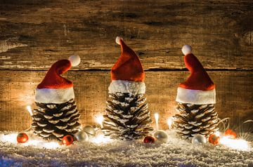 Grappige kerstversiering met dennenappels versierd met rode kerstmutsen, ballen en glimmend licht van Alex Winter
