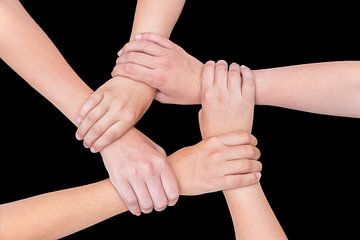 Vijf armen van kinderen houden elkaar vast in cirkel op zwart van