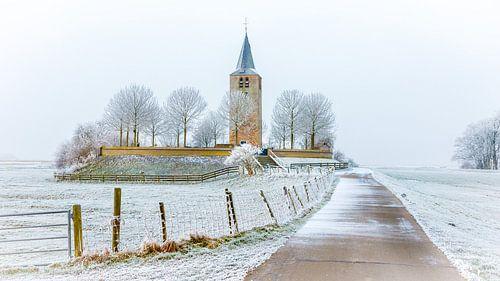 Oude kerktoren in winters landschap van