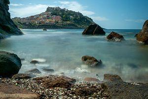 castelsardo in de zee met rotsblokken er voor van