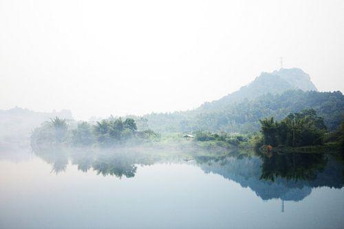 Mistige bergen met op de voorgrond een meer
