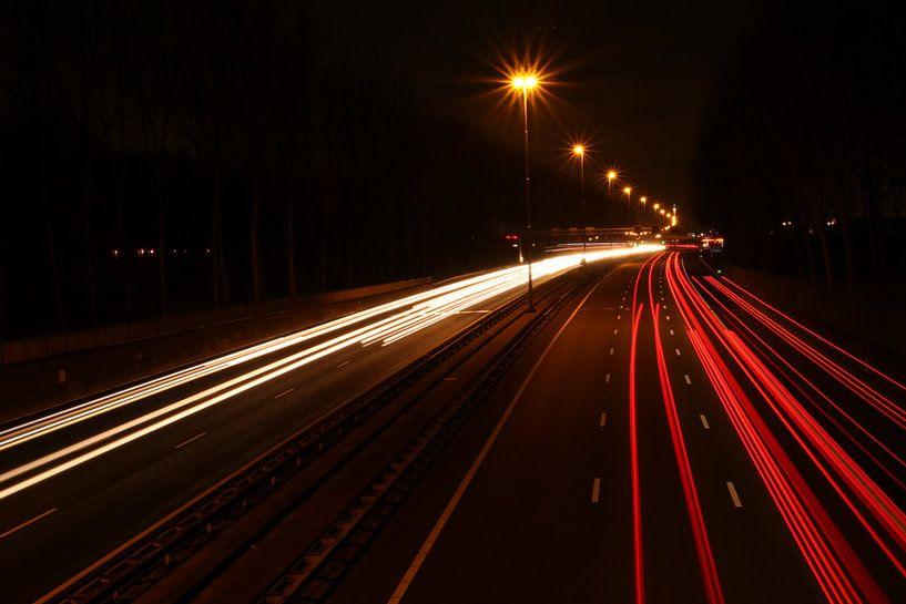 Lichtstrepen boven snelweg A20 van het verkeer in het donker van André Muller