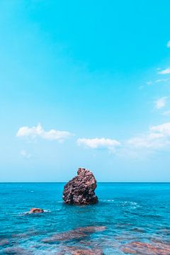 Un rocher solitaire dépasse de l'eau azur. sur MICHEL WETTSTEIN