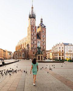 Femme traversant le Grand Marché (Rynek Główny) de la ville polonaise de Cracovie.