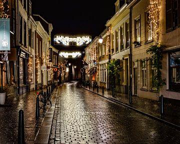 Eine gemütliche Straße in Breda nach einem Regenschauer, die die Lichter schön auf die Straße reflek von