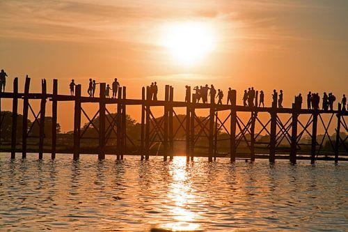 Mensen wandelen op de U Bein brug bij zonsondergang in Mandalay Myanmar van