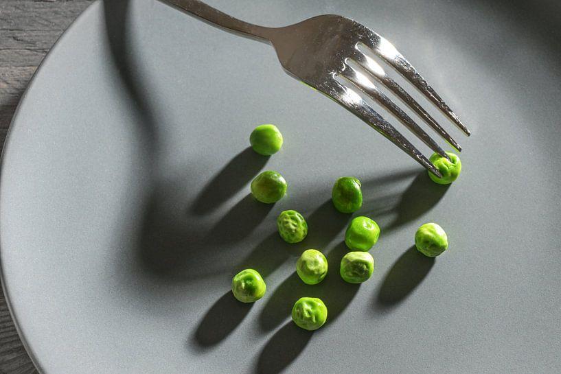 Quelques pois verts et une fourchette avec des ombres sur une assiette grise, un maigre repas de rég sur Maren Winter