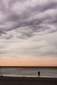 Ein Mensch steht am Strand und genießt nachdenklich die Abendstimmung am Meer