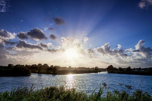 Zonnestralen vanachter de wolken over het water