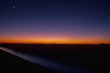 Winterlandschap met maantje bij zonsondergang. van Dick Termond