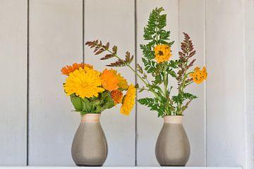Tuin decoreren met goudsbloemen in vaasjes en een wit brocante kastje van J..M de Jong-Jansen
