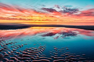 Het strand bij een kleurrijke zonsondergang van eric van der eijk