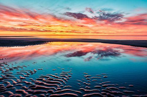 Het strand bij een kleurrijke zonsondergang