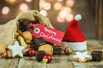 Kerstmis voedsel en snoepjes met tag Merry Christmas en fonkelende lichten achtergrond van Alex Winter
