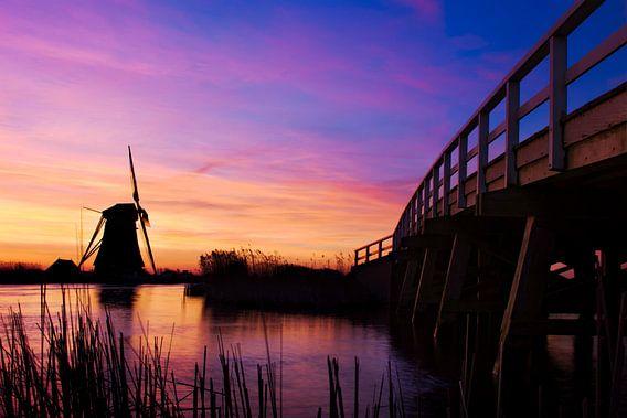 Molen en brug tijdens kleurrijke zonsopkomst