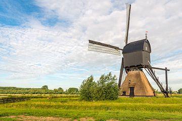 Nederlandse poldermolen contrasterend tegen de bewolkte hemel van Ruud Morijn