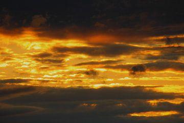 Prachtige zonsondergang door de wolken. van Fabian Engelsman