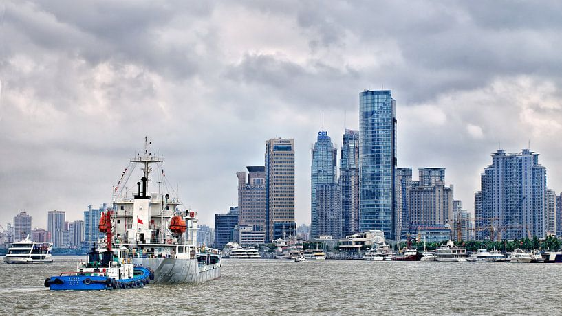 rivier met schepen en de skyline met hoogbouw, Shanghai van Tony Vingerhoets