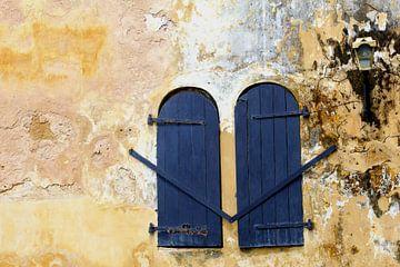 Blauwe luiken in verweerde muur