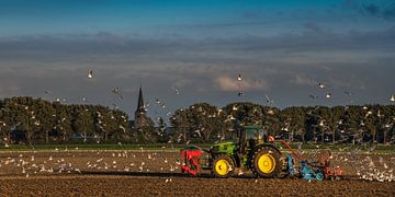 Landbewerken tijdens zonsondergang nabij Sexbierum in Friesland van Harrie Muis