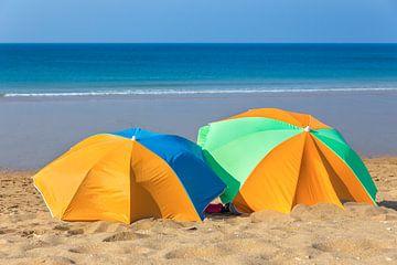 Twee kleurrijke parasols op strand met zee van