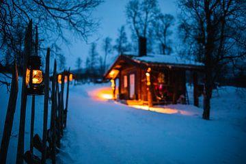 Verlichte houten hut in winterlandschap van Martijn Smeets