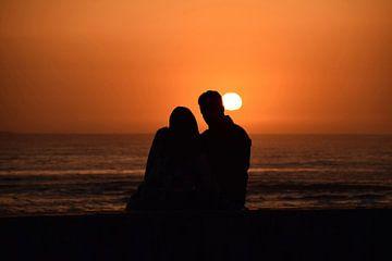 Verliefd koppel aan het staren naar de zonsondergang van Steven Jacobs