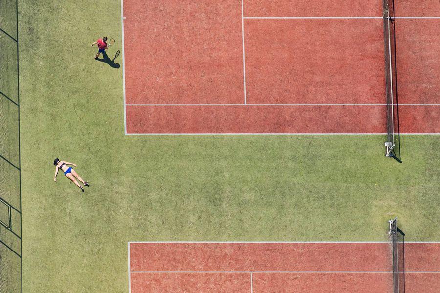 Tennisbaan in vogelvluchtperspectief met een zonnend meisje en een tennisspeler
