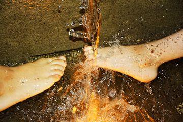 kinderen spelen met hun voeten onder het water van