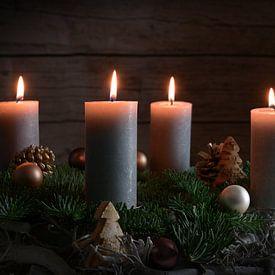 Vier brennende Kerzen auf einem Adventskranz aus Tannenzweigen mit Weihnachtsdekoration vor einer du von Maren Winter