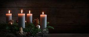 Quatre bougies allumées sur une couronne de l'Avent à partir de branches de sapin avec une décoratio