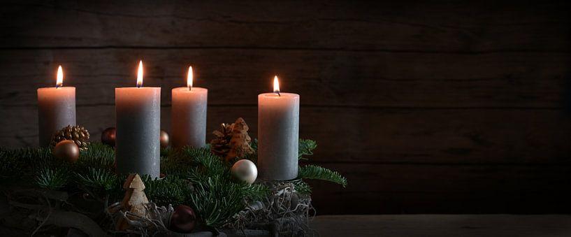 Quatre bougies allumées sur une couronne de l'Avent à partir de branches de sapin avec une décoratio sur Maren Winter