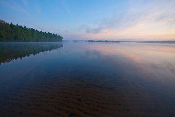 Morgendämmerung auf dem See. Im Vordergrund sieht man durch das Wasser den Sand, die ruhige Wasserob von Michael Semenov