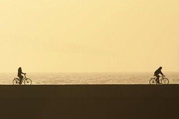 Man en vrouw fietsen bij zonsondergang van Simone Meijer