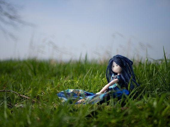 Pop met blauw haar in het gras op een mooie voorjaarsdag