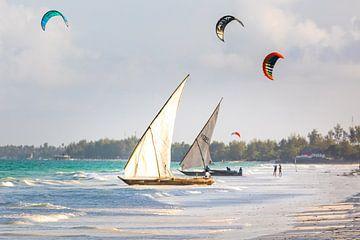Oude traditionele zeilboten op het strand in Zanzibar met kite surfers op de achtergrond van Michiel Ton