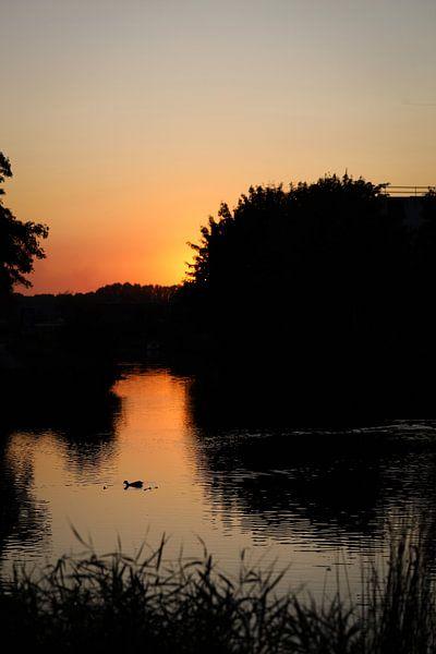 Zonsondergang aan een riviertje van Ken Huysmans