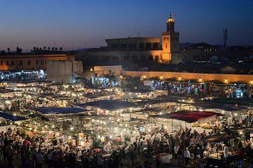 Mensen en voedselkraampjes 's avonds op Jema el Fna in Marrakech Marokko van Dieter Walther
