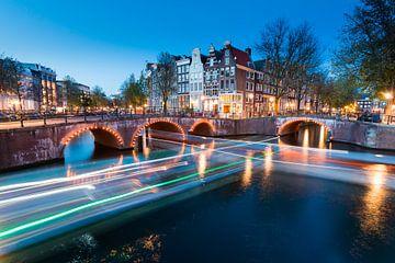 Amsterdamer Grachten mit Brückenlichtern und Bootslichtspuren von Marcel van den Bos