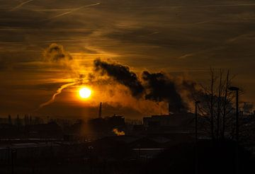 Zonsopgang en fabrieksrook sur Niki Moens